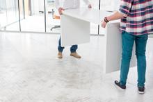 Low Section Of Creative Colleagues Carrying Desk While Setting Up Office