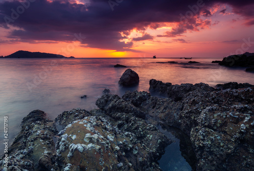 Long exposure image of Dramatic sky and wave seascape with rock in sunset scenery background
