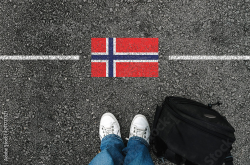 Fototapeta  a man with a shoes and backpack is standing on asphalt next to flag of Norway and border obraz