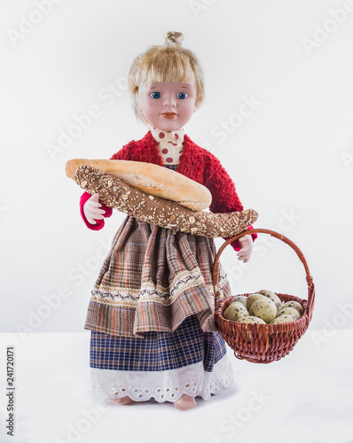 Fotografie, Obraz  Girl-Doll toy with bread and basket with quail eggs