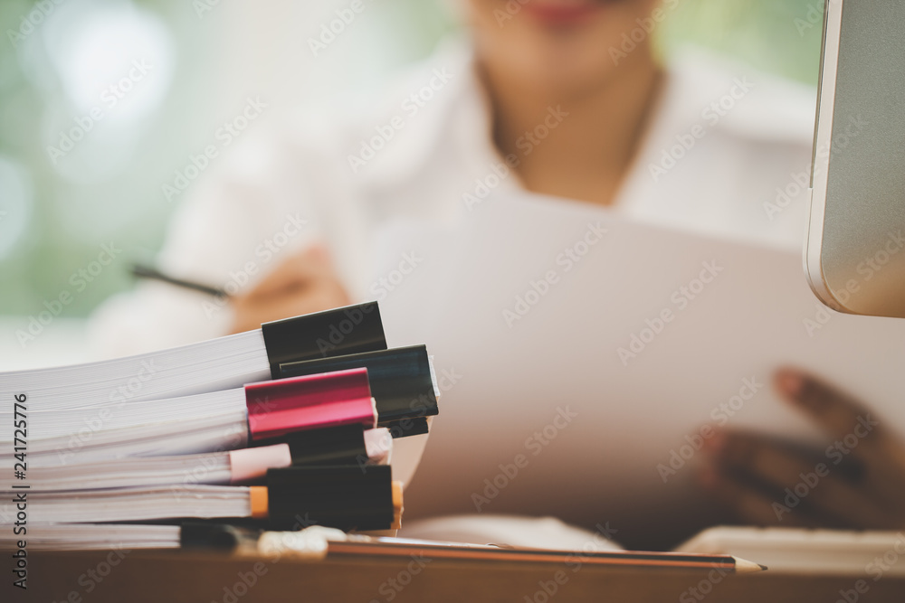 Fototapeta Accounting planning budget report file concept : Business woman offices check working for arranging documents unfinished stack of document paperwork with pen on busy office with pc computer.