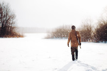 Man Securing A Reserve. Man Walking On A Snowy Day. Copy Space. Back View Shot