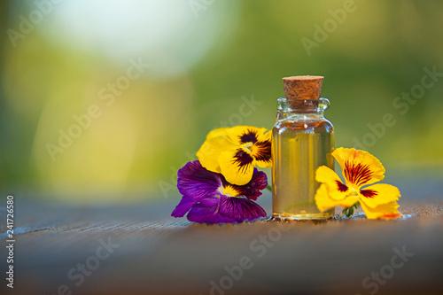 Papiers peints Pansies pansies essential oil in beautiful bottle on wooden background