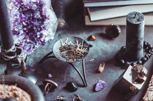 Smoked herbs on a witch's altar for a magical ritual among crystals and black candles Fototapeta