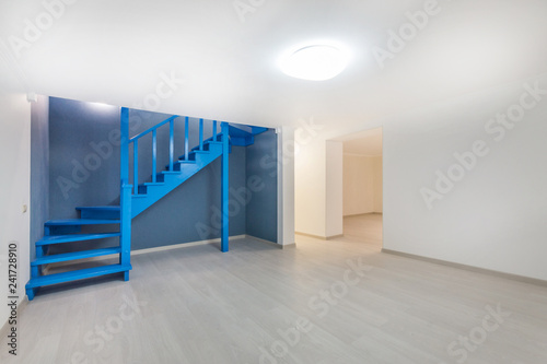 Empty basement room with laminate flooring, high ceiling and deep blue wooden st Fototapete