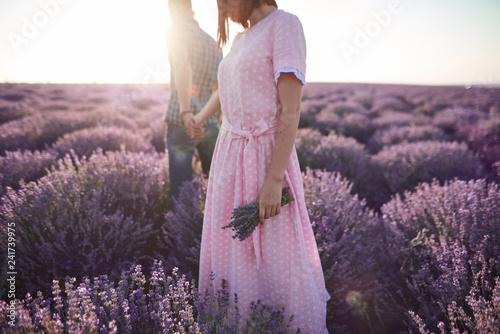 Młoda dziewczyna w romantycznej sukience i jej mężczyzna w polach lawendy