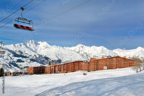 ski slopes in french alps resort and chair lift under blue sky