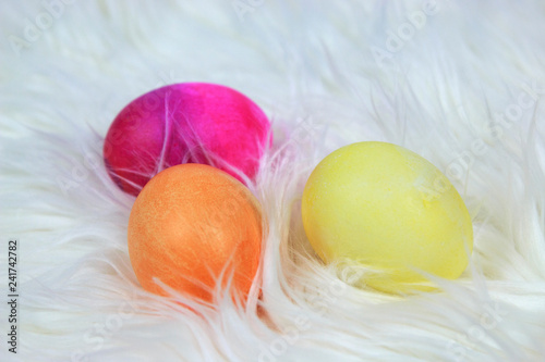 Fotografie, Obraz  Colorful dyed Easter Eggs laying on white Soft Fur