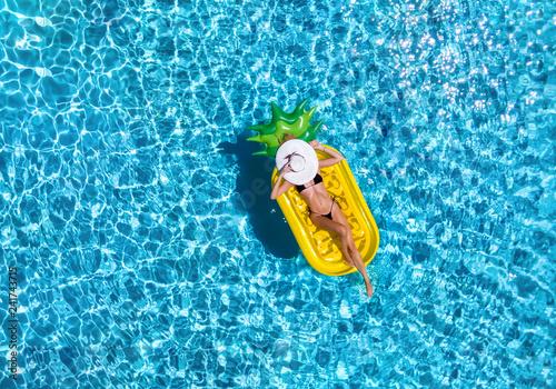 Fotografie, Obraz  Junge Frau im Bikini mit Sonnenhut entspannt auf einer Luftmatratze in Ananasfor