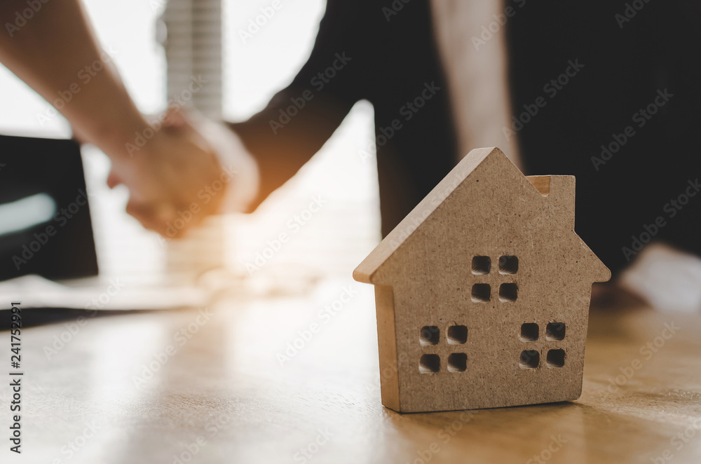 Fototapeta real estate broker manager hand shake to customer after signing contract for buying house in estate agent office behind House model, investment, home loan contract, buy and sell house concept