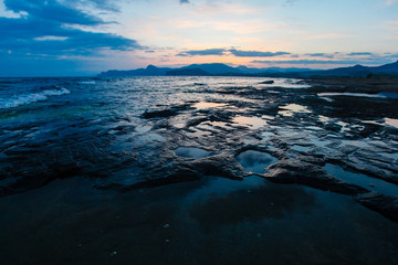 Rocky shore washed by sea waves in evening. Marine landscape