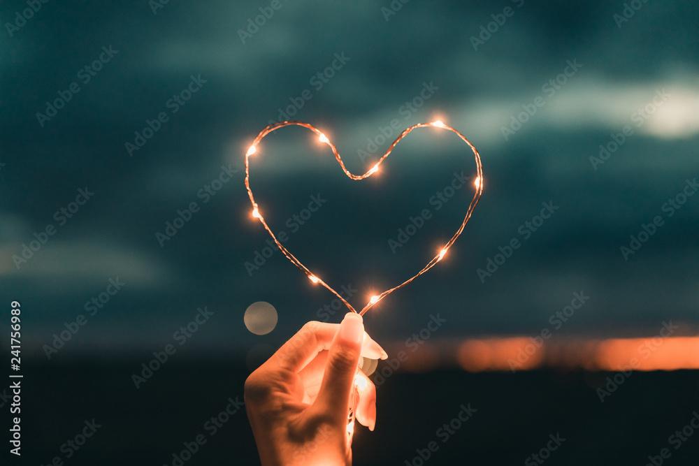 Fototapety, obrazy: Simbolo del cuore fatto da una striscia di luci led tenuto da una mano di una ragazza di fronte al cielo sfuocato. San Valentino concetto.