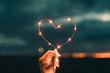 Simbolo del cuore fatto da una striscia di luci led tenuto da una mano di una ragazza di fronte al cielo sfuocato. San Valentino concetto.