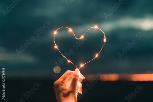 Fotografie, Obraz Simbolo del cuore fatto da una striscia di luci led tenuto da una mano di una ragazza di fronte al cielo sfuocato
