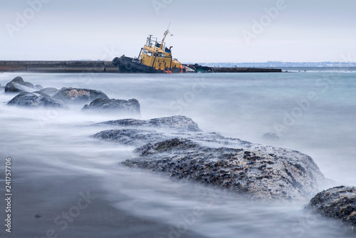Tuinposter Poort stones on the beach and flooded tug boat