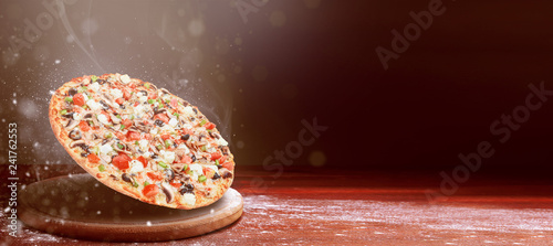 classic pizza on a dark wooden table background and a scattering of flour. pizza restaurant menu concept