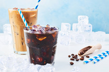 Summer Drink Iced Coffee In A Glass And Ice Coffee With Cream In A Tall Glass, Coffee Beans And Straws Surrounded By Ice On White Marble Table Over Blue Background. Copy Space For Text.