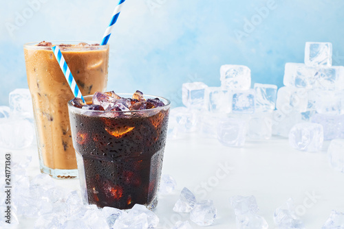 Fotografía Summer drink iced coffee in a glass and ice coffee with cream in a tall glass surrounded by ice on white marble table over blue background