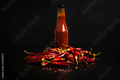 Poster Hot chili peppers Chilli peppers and bottles of spicy sauce