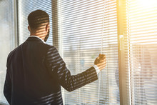 The Man Standing Near The Office Window With Jalousie