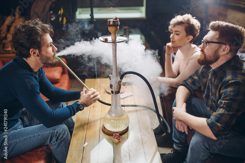 Group of young cheerful friends relaxing in shisha club. close up photo.entertainment. time with best friends