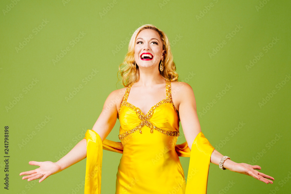 Photo  Enjoying the limelight, an elegant blonde with arms out, isolated on green studi