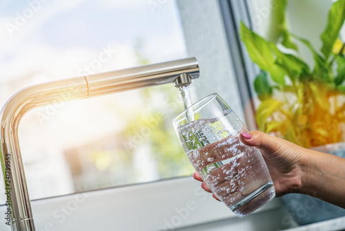 Fototapety, obrazy: Woman filling a glass of water from a stainless steel or chrome tap or faucet, close up on her hand and the glass with running water and air bubbles