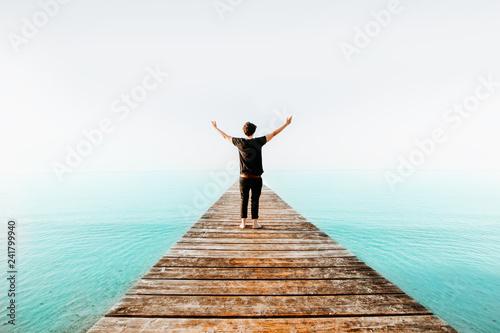 Fotografie, Obraz  Person breitet Arme am dem Meer auf einem Holz Steg aus