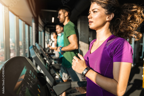 Poster Fitness Young focused woman running on a treadmill in a gym