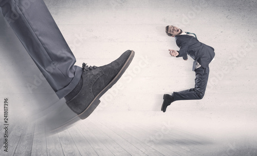 Fotografie, Obraz Big foot in a black shoe fire small, young, businessman who is flying away in th