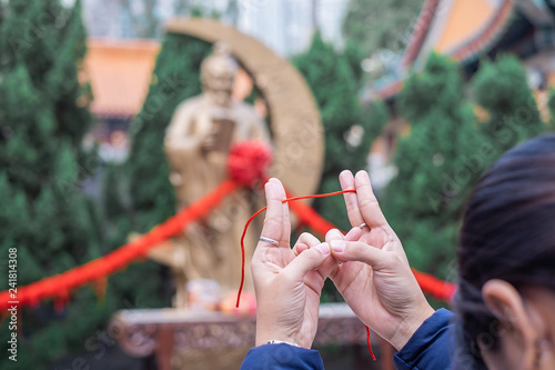 Fényképezés Young woman ties red rope and pray at Yue Lao (God of marriage) in Wong Tai Sin Temple, is well known for love and marriage prayers answered