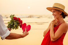 Happy Beautiful Woman In Red Dress Receiving A Gift From A Man By Sea Sunset.surprise Wife From Husband Bouquet Of Roses Women's Day March 8 And Valentine's Day.engagement Love At First Sight Romantic