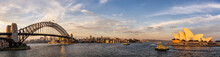 Panoramic View Of Sydney Harbor Bridge And Opera House With Boats Sailing In The Bay And Downtown In The Background At Sunset