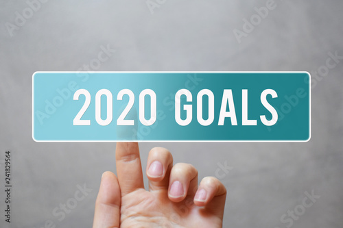 Fotografia  2020 goals - finger pressing blue transparent button on virtual touchscreen interface on gray background with copy space for text