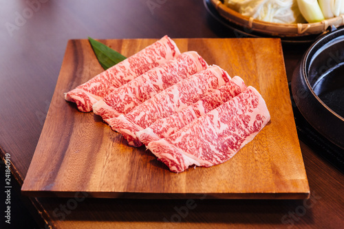 Premium Rare Slices Wagyu A5 beef with high-marbled texture on square wooden plate served for Sukiyaki and Shabu.