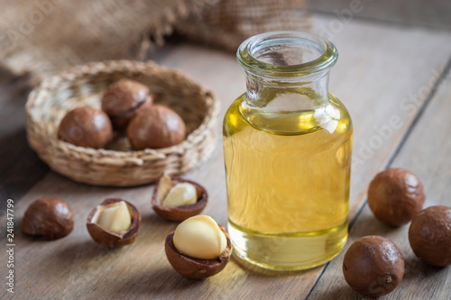 Foto op Canvas Kruiderij Macadamia oil in bottle and macadamia nuts on wooden table.