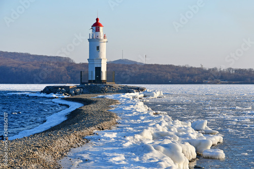 Russia. Vladivostok. The lighthouse of Egersheld(1876 year built) Tokarevskaya koshka in winter evening in Amur bay