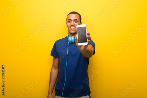 African american man with blue t-shirt on yellow background looking at the camera and smiling while using the mobile - 241862537