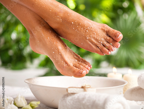 Foot spa on a tropical green leaves background
