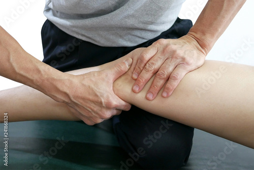 Fotografie, Obraz Physical therapist hands treat the knee to the patient on bed