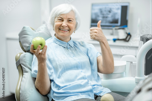 Canvas Print Portrait of a beautiful senior woman with healthy smile holding green apple at t