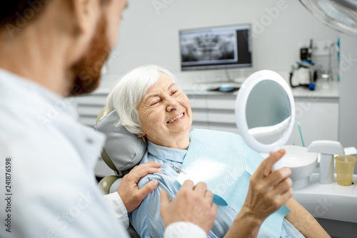 Spoed Foto op Canvas Hoogte schaal Happy elderly woman enjoying her beautiful toothy smile looking to the mirror in the dental office