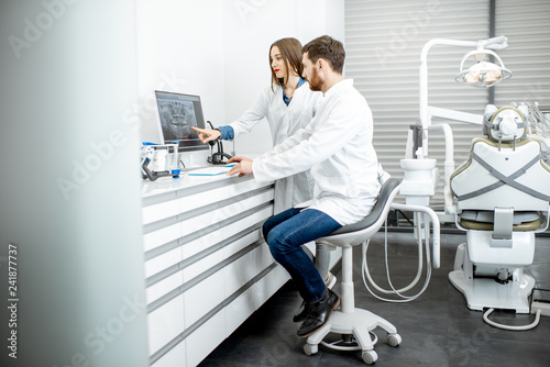 Dentist with young woman assistant working with computer in the dental office