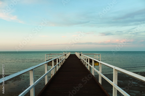 Foto op Plexiglas Panoramafoto s Wooden pier during sunset overseeing the ocean with orange clouds and turquoise sky (Hervey Bay near Fraser Island, Queensland, Australia)