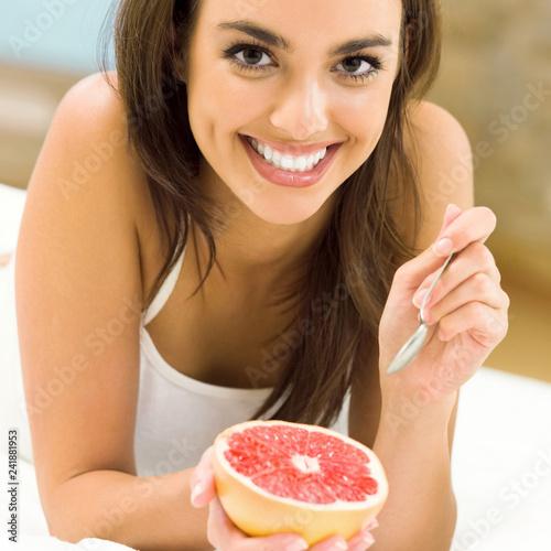 Portarit of young woman eating grapefruit at home