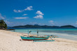 Tropical background view from Malcapuya island with traditional philippines boat and white sand beach. Travel vacation at Philippines.