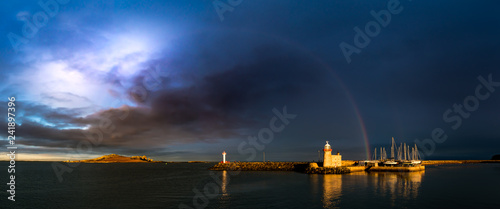 Panorama of Howth Harbour in County Dublin under a dramatic stormy cloudy sky with a rainbow spreading from the Eye of Ireland across to a lighthouse and moored sailing boats bathed in sunlight Canvas Print