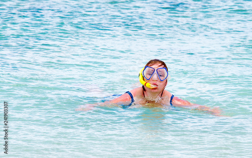 Overweight woman swimming and snorkeling during summer vacations.