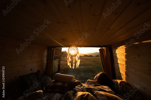 Fotomural Beautiful view from camper van during sunrise in summer with woman in a bed