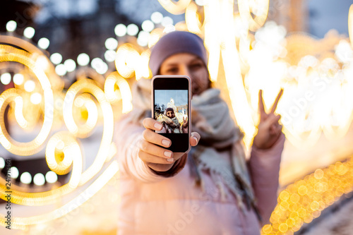 Fotografiet  Woman taking selfie in front of the christmas lite decor outdoors